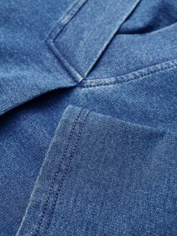 Frau trägt Kleid in Kokon-Passform von THOUGHT (SKYLAR LOOPBACK) aus Biobaumwolle in Denim-Optik mit V-Ausschnitt, versteckten Tasche und dreiviertellangen Kimonoärmeln. Loopback-Stoff mit natürlichem Indigo gefärbt. / Detailansicht 2 / pussyGALORE / Leipzig