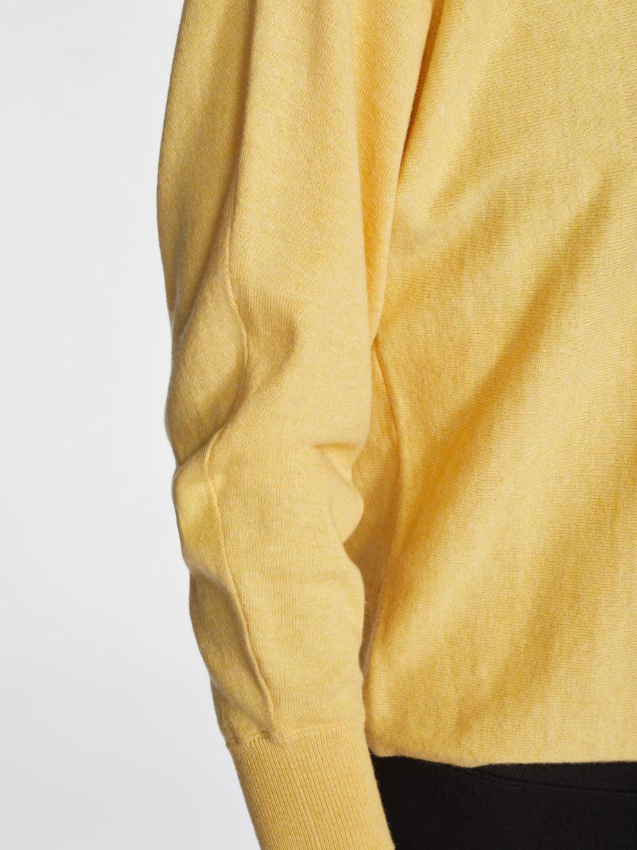 Frau trägt zitronengelben Pullover von THOUGHT (POLLY DOLMAN) mit Rundhals-Ausschnitt und Fledermausärmeln aus Biobaumwolle und Wolle in tailliertem Schnitt / Lemon Yellow / Detailansicht / pussyGALORE / Leipzig