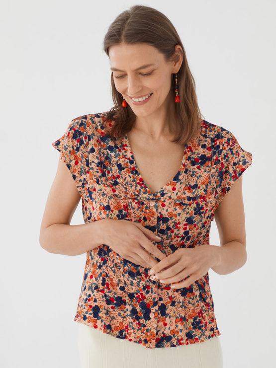 Frau trägt Bluse aus Viskose mit floralem Muster von NICE THINGS (MILLEFIORI PRINT) mit doppeltem Reverskragen, Knopfleiste und kurzen Ärmeln. / Bauhaus / pussyGALORE / Leipzig