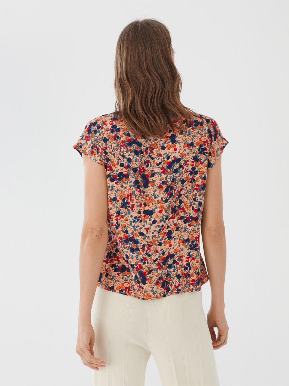 Frau trägt Bluse aus Viskose mit floralem Muster von NICE THINGS (MILLEFIORI PRINT) mit doppeltem Reverskragen, Knopfleiste und kurzen Ärmeln. / Bauhaus / Rückenansicht/ pussyGALORE / Leipzig