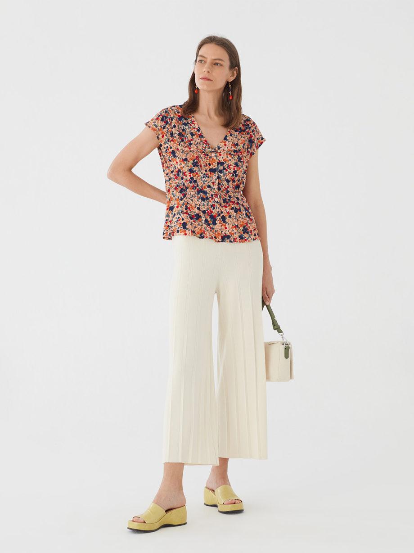 Frau trägt Bluse aus Viskose mit floralem Muster von NICE THINGS (MILLEFIORI PRINT) mit doppeltem Reverskragen, Knopfleiste und kurzen Ärmeln. / Bauhaus / Vorderansicht 1 / pussyGALORE / Leipzig