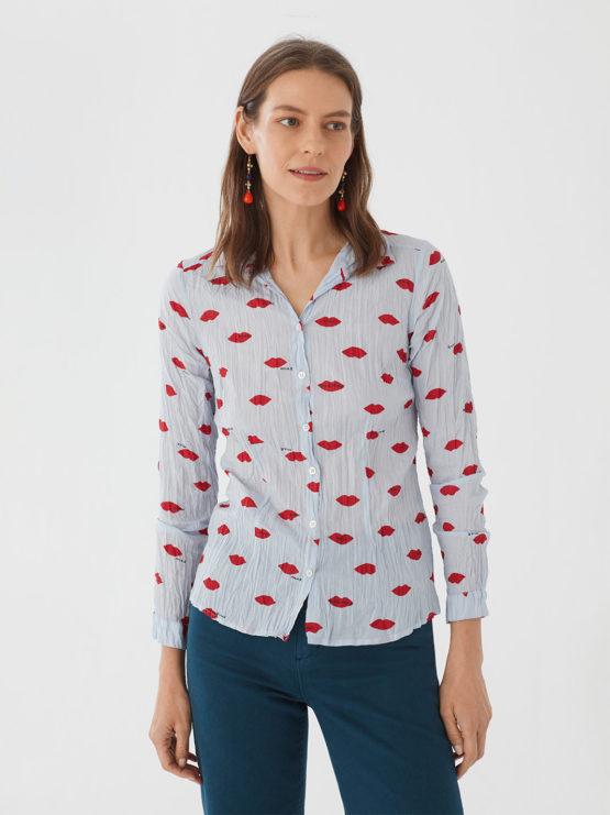 Frau trägt langärmlige taillierte Bluse aus nachhaltiger gecrinkelter Baumwolle von NICE THINGS (LIPS PRINT) in Hellblau mit Muster aus roten Lippen, Hemdkragen und passendem Stoffbeutel. / Adieu Tristesse / Vorderansicht / pussyGALORE / Leipzig