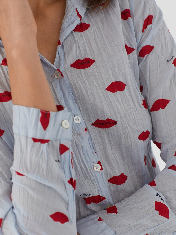 Frau trägt langärmlige taillierte Bluse aus nachhaltiger gecrinkelter Baumwolle von NICE THINGS (LIPS PRINT) in Hellblau mit Muster aus roten Lippen, Hemdkragen und passendem Stoffbeutel. / Adieu Tristesse / Detailansicht 2 / pussyGALORE / Leipzig