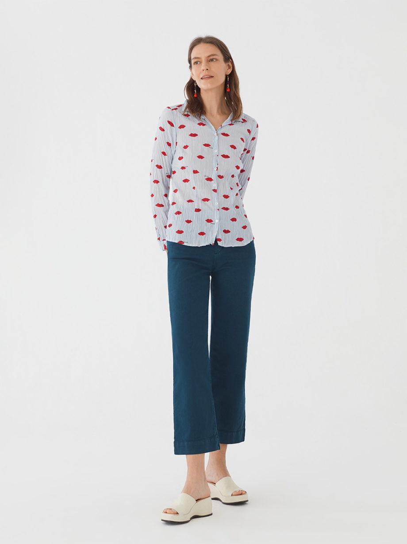 Frau trägt langärmlige taillierte Bluse aus nachhaltiger gecrinkelter Baumwolle von NICE THINGS (LIPS PRINT) in Hellblau mit Muster aus roten Lippen, Hemdkragen und passendem Stoffbeutel. / Adieu Tristesse / Vorderansicht 1 / pussyGALORE / Leipzig
