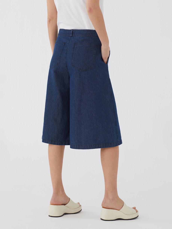 Frau trägt weite Culotte aus Denim von NICE THINGS (DENIM CULOTTE) mit Reißverschluss, seitlichen Eingriffstaschen, aufgesetzten Taschen hinten und Gürtelschlaufen. / Peaceful Mood / Rückenansicht / pussyGALORE / Leipzig