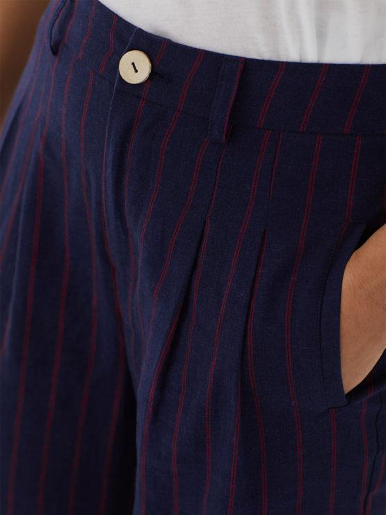 Frau trägt lange dunkelblaue Hose von NICE THINGS (DIPLO STRIPED) mit roten Nadelstreifen aus Leinen-Viskose-Mischung mit Bundfalten und Knopf aus Kokosnuss. / Adieu Tristesse / Detailansicht / pussyGALORE / Leipzig