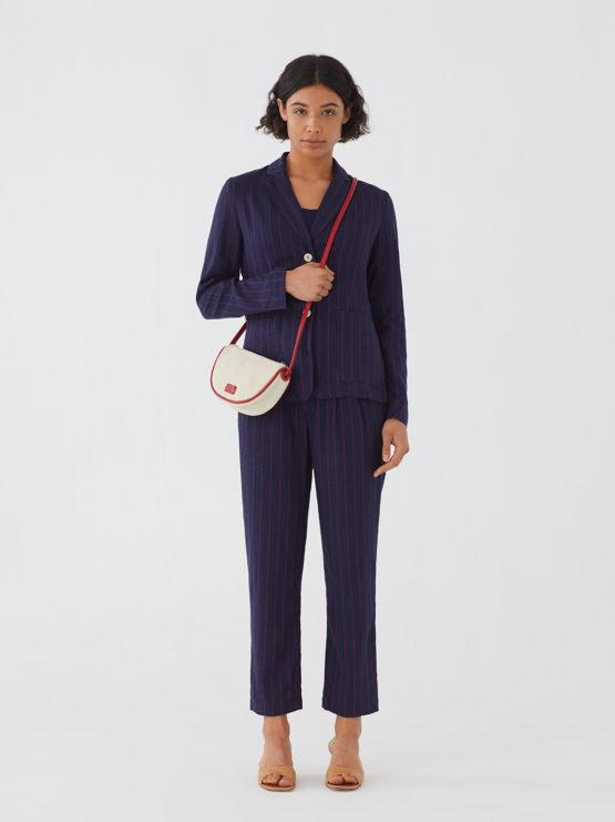 Frau trägt lange dunkelblaue Hose von NICE THINGS (DIPLO STRIPED) mit roten Nadelstreifen aus Leinen-Viskose-Mischung mit Bundfalten und Knopf aus Kokosnuss. / Adieu Tristesse / Vorderansicht 2 / pussyGALORE / Leipzig