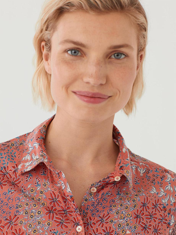 Frau trägt langärmlige taillierte Bluse aus nachhaltiger gecrinkelter Baumwolle von NICE THINGS (PEACEFUL GARDEN PRINT) in Korallrot mit floralem Muster, Hemdkragen und passendem Stoffbeutel. / Peaceful Mood / Detailansicht 2 / pussyGALORE / Leipzig