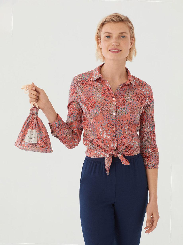 Frau trägt langärmlige taillierte Bluse aus nachhaltiger gecrinkelter Baumwolle von NICE THINGS (PEACEFUL GARDEN PRINT) in Korallrot mit floralem Muster, Hemdkragen und passendem Stoffbeutel. / Peaceful Mood / Vorderansicht 2 / pussyGALORE / Leipzig