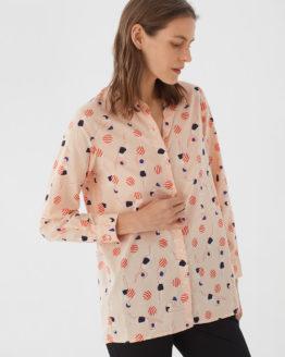 Frau trägt Bluse aus nachhaltiger Baumwolle von NICE THINGS (SWIMMERS PRINT) in Apricot mit grafischem Schwimmerinnen Print, Hemdkragen und langen Ärmeln. / Bauhaus / Vorderansicht 2 / pussyGALORE / Leipzig