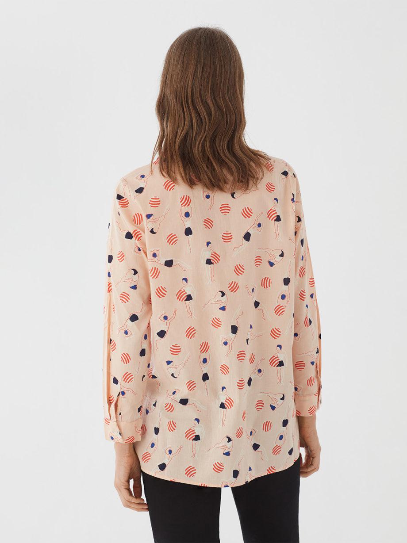 Frau trägt Bluse aus nachhaltiger Baumwolle von NICE THINGS (SWIMMERS PRINT) in Apricot mit grafischem Schwimmerinnen Print, Hemdkragen und langen Ärmeln. / Bauhaus / Rückenansicht / pussyGALORE / Leipzig