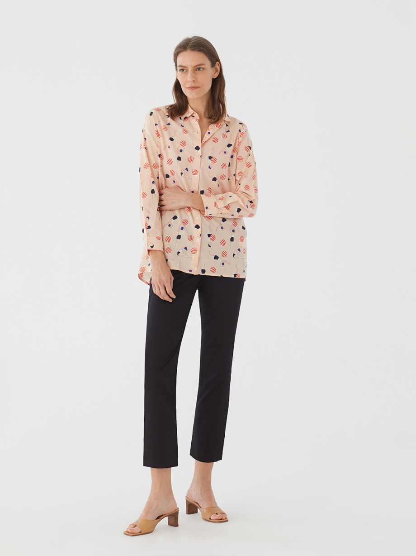 Frau trägt Bluse aus nachhaltiger Baumwolle von NICE THINGS (SWIMMERS PRINT) in Apricot mit grafischem Schwimmerinnen Print, Hemdkragen und langen Ärmeln. / Bauhaus / Vorderansicht 3 / pussyGALORE / Leipzig