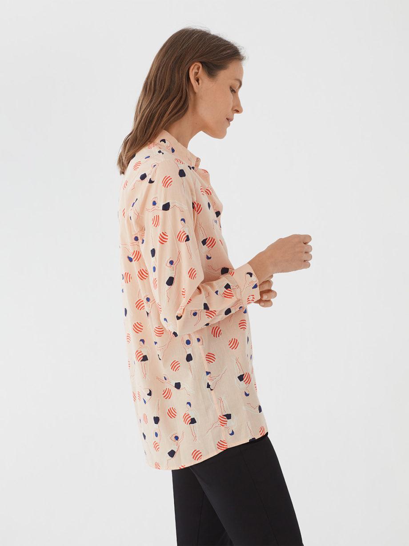 Frau trägt Bluse aus nachhaltiger Baumwolle von NICE THINGS (SWIMMERS PRINT) in Apricot mit grafischem Schwimmerinnen Print, Hemdkragen und langen Ärmeln. / Bauhaus / Seitenansicht / pussyGALORE / Leipzig