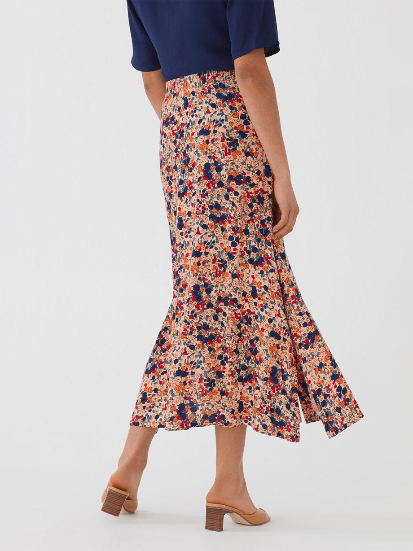 Frau trägt Maxirock aus Viskose mit floralem Muster von NICE THINGS (MILLEFIORI PRINT) aus Viskose mit Knopfleiste, Gummizug und seitlichen Schlitzen. / Bauhaus/ Rückenansicht / pussyGALORE / Leipzig