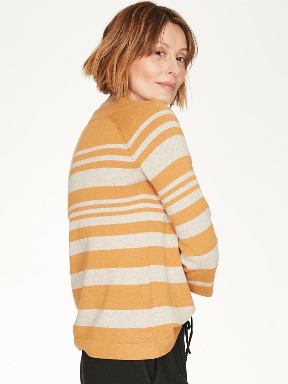 Frau trägt gestreiften Strickpullover von THOUGHT (SAIL LA VIE) aus Biobaumwolle und Wolle mit U-Boot-Ausschnitt und dreiviertellangen Raglanärmeln. / Amber / Seitenansicht / pussyGALORE / Leipzig