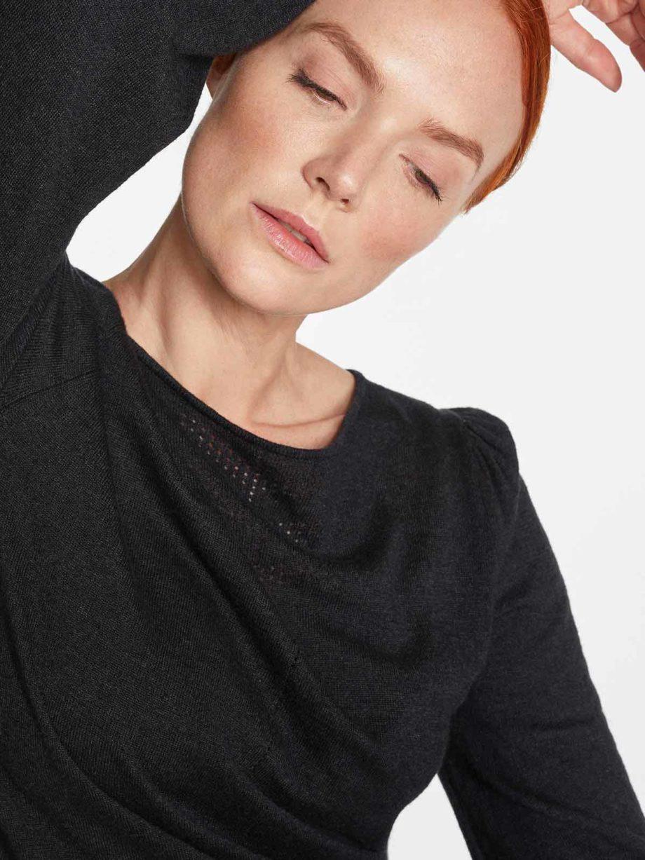 Frau trägt dunkelgrauen leichten Strickpullover von THOUGHT (EVADNE) aus Tencel, Viskose und Wolle mit Pointelle-Lochmuster und Ballonärmeln. / pussyGALORE / Leipzig