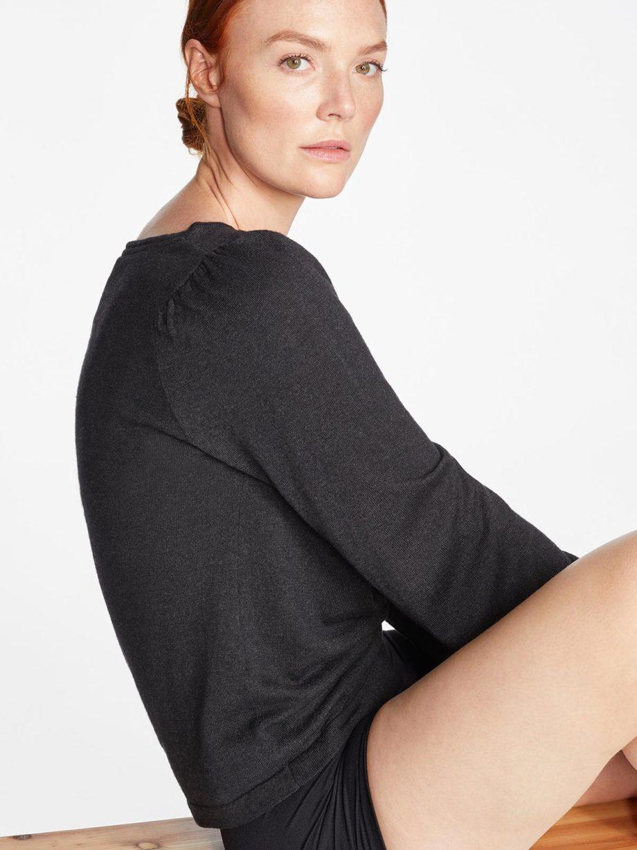 Frau trägt dunkelgrauen leichten Strickpullover von THOUGHT (EVADNE) aus Tencel, Viskose und Wolle mit Pointelle-Lochmuster und Ballonärmeln. / Seitenansicht / pussyGALORE / Leipzig