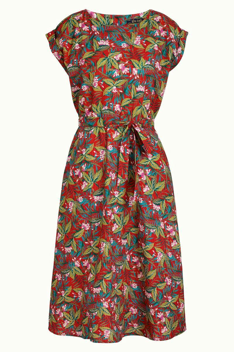 Ausgestelltes Kleid von KING LOUIE (BETTY LOOSE FIT DRESS SALINA) in Midi-Länge aus Baumwolle und Viskose in Seersucker-Qualität mit floralem Muster in Rosa und Grün auf rotem Grund. Gummizug in der Taille, Bindegürtel, seitliche Eingriffstaschen, U-Boot-Ausschnitt, angeschnittene Ärmel und Zierknopfleiste hinten. / 645 Red / Detailansicht 2 / pussyGALORE / Leipzig