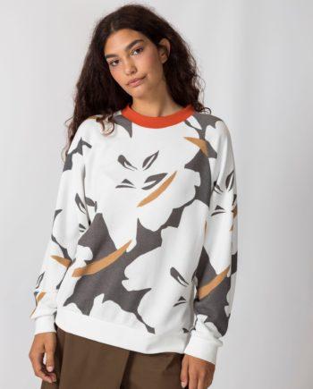Frau trägt Pullover von SKFK (KORE) aus Biobaumwolle mit abstrahiertem floralem Aufdruck in Naturweiß, Ockergelb und Dunkelgrau mit orangenem Rundhals-Ausschnitt. Sportliche Sweatshirt-Passform mit gerippten Bündchen. / Color 2N / pussyGALORE / Leipzig