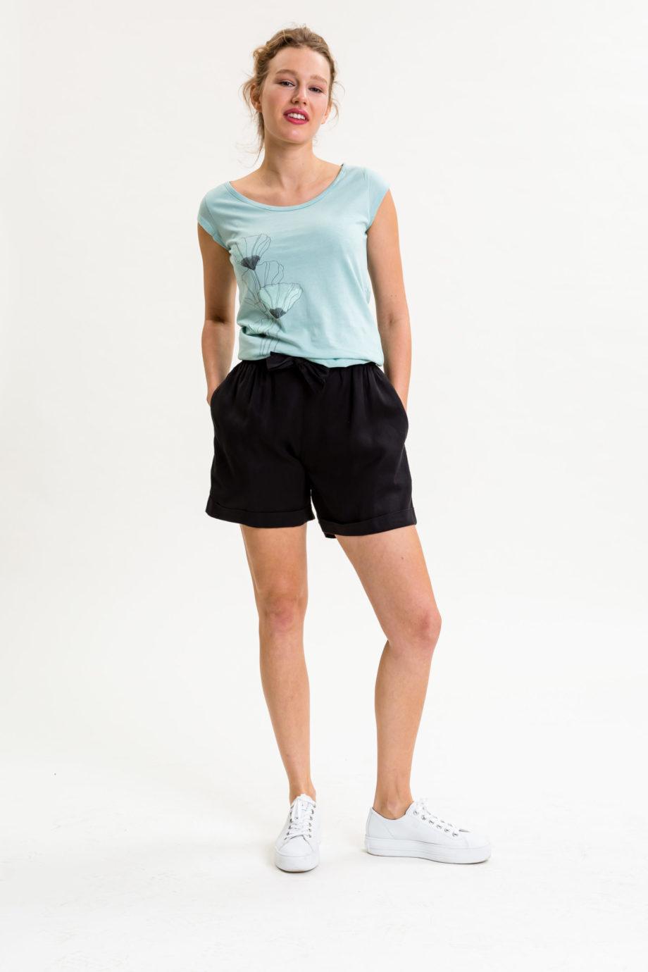 Frau trägt kurze Hose von UVR CONNECTED (CORYINA) aus Tencel mit elastischem Bund, Hosenaufschlag, Schleifenband, weit geschnittenem Bein und Seitentaschen. Fair produziert in Europa. / Schwarz / Vorderansicht / pussyGALORE / Leipzig