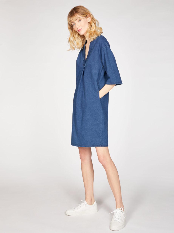 Frau trägt Kleid in Kokon-Passform von THOUGHT (SKYLAR LOOPBACK) aus Biobaumwolle in Denim-Optik mit V-Ausschnitt, versteckten Tasche und dreiviertellangen Kimonoärmeln. Loopback-Stoff mit natürlichem Indigo gefärbt. / Seitenansicht / pussyGALORE / Leipzig