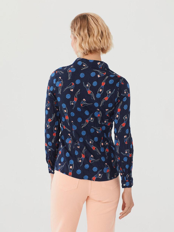 Frau trägt langärmlige taillierte Bluse aus nachhaltiger gecrinkelter Baumwolle von NICE THINGS (SWIMMERS PRINT) in Navy mit grafischem Schwimmerinnen Print, Hemdkragen und passendem Stoffbeutel / Bauhaus / Rückenansicht / pussyGALORE / Leipzig