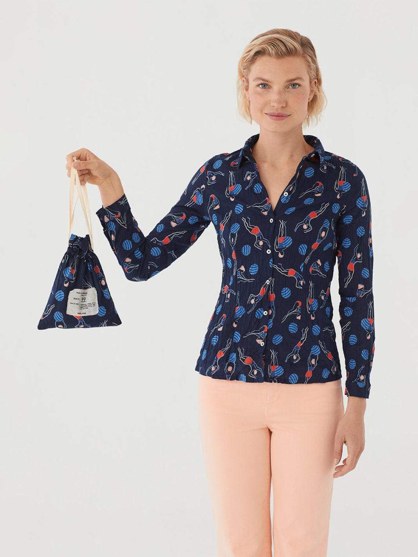 Frau trägt langärmlige taillierte Bluse aus nachhaltiger gecrinkelter Baumwolle von NICE THINGS (SWIMMERS PRINT) in Navy mit grafischem Schwimmerinnen Print, Hemdkragen und passendem Stoffbeutel / Bauhaus / Vorderansicht / pussyGALORE / Leipzig
