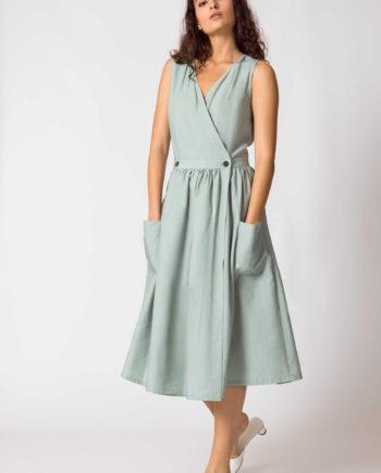 Frau trägt ärmelloses Wickelkleid von SKFK (GABRIELA) aus Lycocell in hellem Mintgrün. Oben figurnah mit V-Ausschnitt, unten ausgestellter Rock in A-Linie und Midi-Länge mit zwei Knöpfen in der Taille zum verschliessen und aufgesetzten Taschen vorn. / Color G4 / pussyGALORE / Leipzig