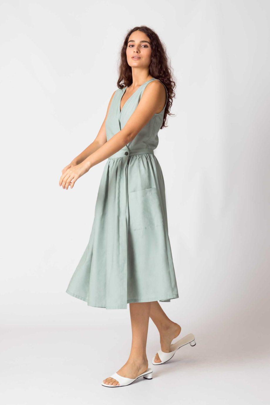 Frau trägt ärmelloses Wickelkleid von SKFK (GABRIELA) aus Lycocell in hellem Mintgrün. Oben figurnah mit V-Ausschnitt, unten ausgestellter Rock in A-Linie und Midi-Länge mit zwei Knöpfen in der Taille zum verschliessen und aufgesetzten Taschen vorn. / Color G4 / Seitenansicht / pussyGALORE / Leipzig
