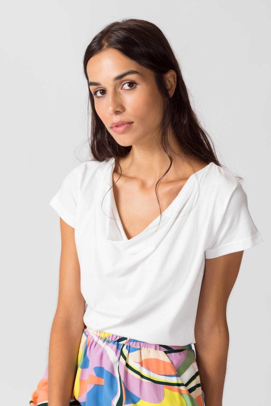 Frau trägt Shirt von SKFK (BAT) aus Biobaumwolle mit kurzen Ärmeln und Wasserfall-Ausschnitt. GOTS und Fairtrade zertifiziert. / Weiß / Vorderansicht / pussyGALORE / Leipzig