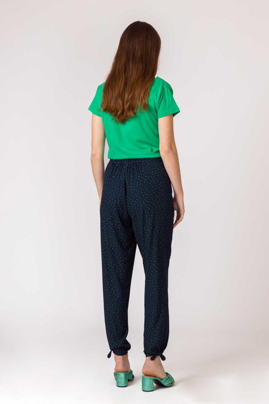Frau trägt Shirt von SKFK (BAT) aus Biobaumwolle mit kurzen Ärmeln und Wasserfall-Ausschnitt. GOTS und Fairtrade zertifiziert. / Grün / Rückenansicht / pussyGALORE / Leipzig