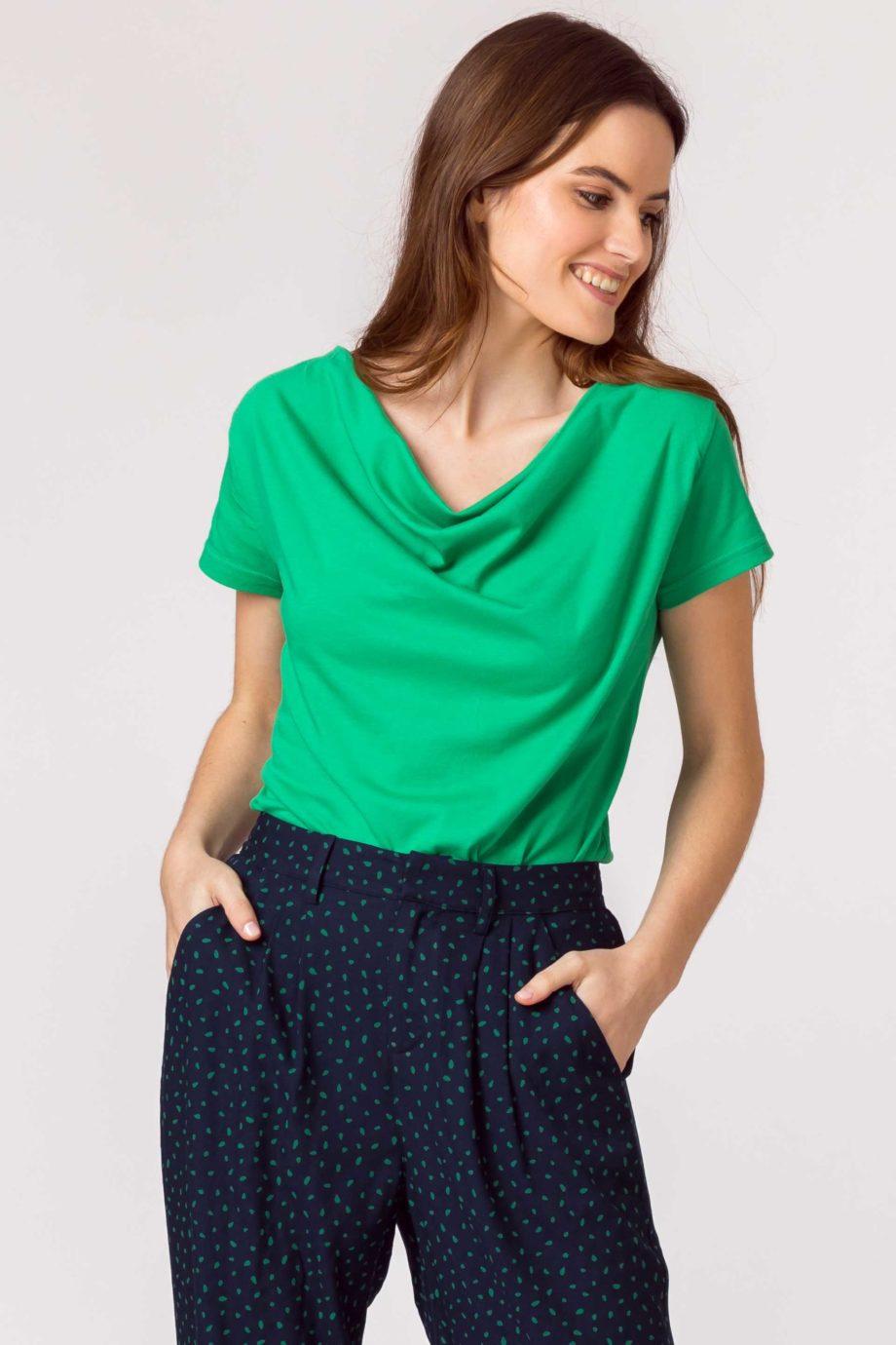 Frau trägt Shirt von SKFK (BAT) aus Biobaumwolle mit kurzen Ärmeln und Wasserfall-Ausschnitt. GOTS und Fairtrade zertifiziert. / Grün / Vorderansicht / pussyGALORE / Leipzig
