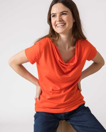 Frau trägt Shirt von SKFK (BAT) aus Biobaumwolle mit kurzen Ärmeln und Wasserfall-Ausschnitt. GOTS und Fairtrade zertifiziert. / Weiß, Orange, Grün / pussyGALORE / Leipzig