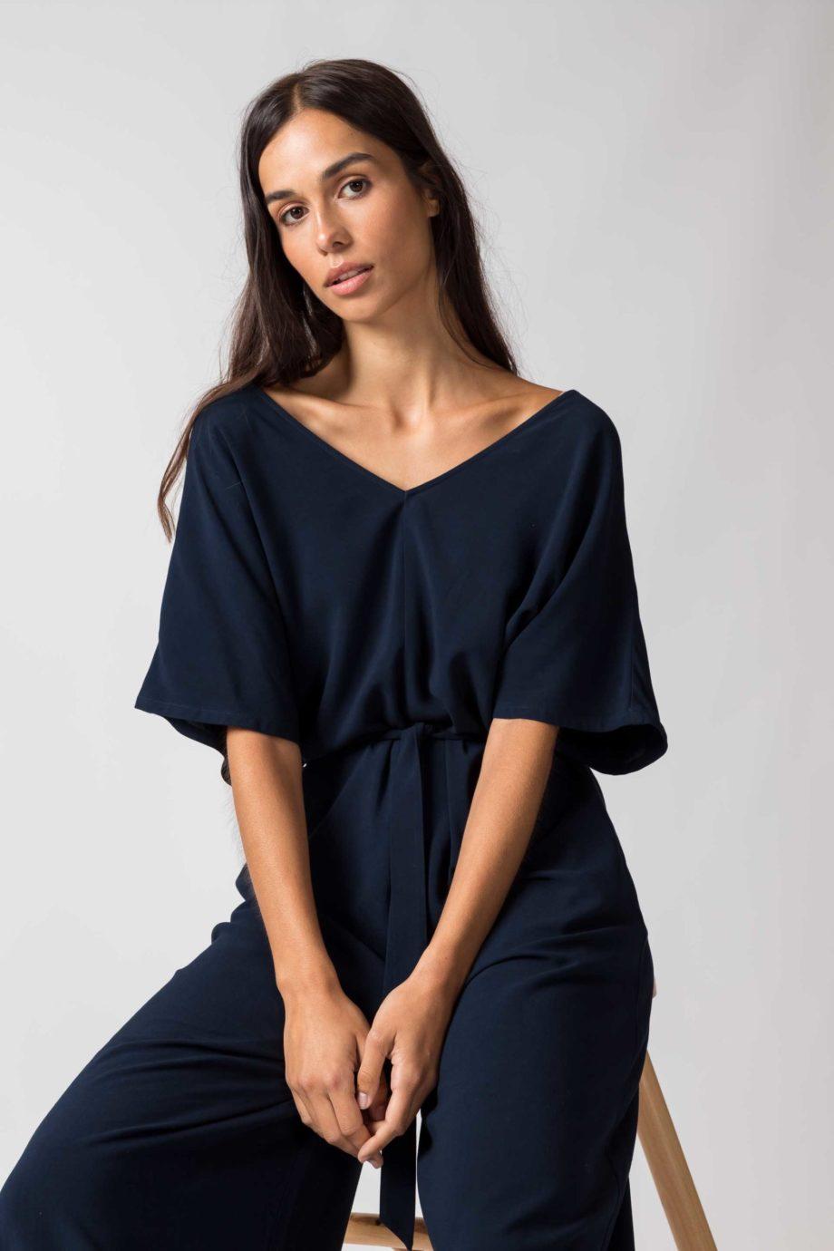 Frau trägt dunkelblauen Jumpsuit von SKFK (KARITATE) aus recycelter Viskose mit kurzen Ärmeln, V-Ausschnitt vorn und hinten und seitlichen Eingriffstaschen. Nobel und bequem - der weite Schnitt mit abnehmbarem Bindegürtel. / Detailansicht / Color B8 / pussyGALORE / Leipzig