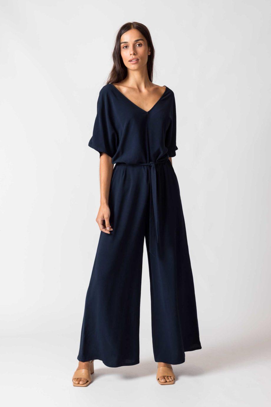 Frau trägt dunkelblauen Jumpsuit von SKFK (KARITATE) aus recycelter Viskose mit kurzen Ärmeln, V-Ausschnitt vorn und hinten und seitlichen Eingriffstaschen. Nobel und bequem - der weite Schnitt mit abnehmbarem Bindegürtel. / Color B8 / pussyGALORE / Leipzig