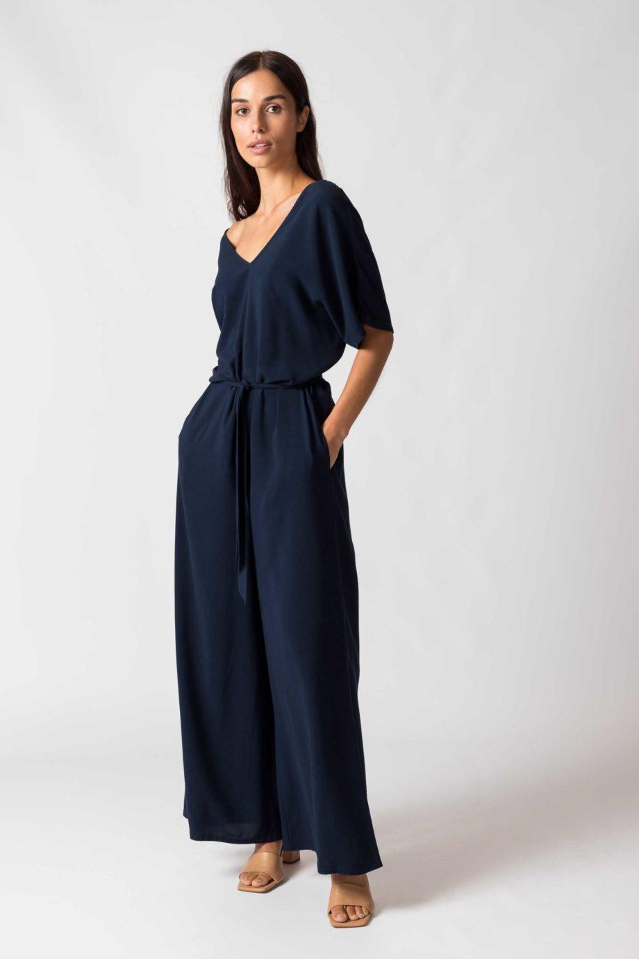 Frau trägt dunkelblauen Jumpsuit von SKFK (KARITATE) aus recycelter Viskose mit kurzen Ärmeln, V-Ausschnitt vorn und hinten und seitlichen Eingriffstaschen. Nobel und bequem - der weite Schnitt mit abnehmbarem Bindegürtel. / Seitenansicht / Color B8 / pussyGALORE / Leipzig