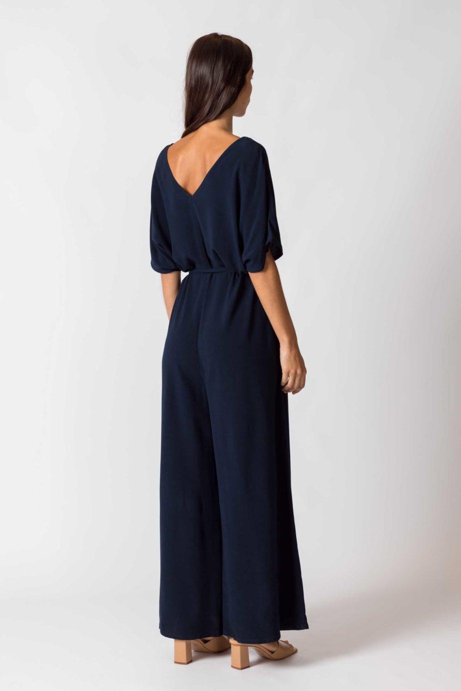 Frau trägt dunkelblauen Jumpsuit von SKFK (KARITATE) aus recycelter Viskose mit kurzen Ärmeln, V-Ausschnitt vorn und hinten und seitlichen Eingriffstaschen. Nobel und bequem - der weite Schnitt mit abnehmbarem Bindegürtel. / Rückenansicht / Color B8 / pussyGALORE / Leipzig