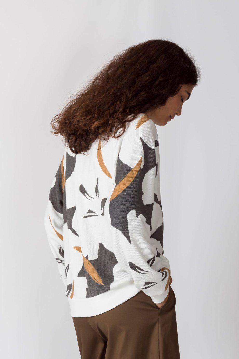 Frau trägt Pullover von SKFK (KORE) aus Biobaumwolle mit abstrahiertem floralem Aufdruck in Naturweiß, Ockergelb und Dunkelgrau mit orangenem Rundhals-Ausschnitt. Sportliche Sweatshirt-Passform mit gerippten Bündchen. / Color 2N / Vorderansicht / pussyGALORE / Leipzig